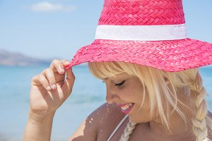 Blond woman with red hat in summer.