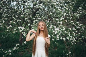 Portrait of beautiful young woman in apple trees blooming. Stylish girl in white dress with apple trees flowers