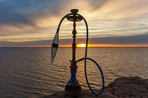 Hookah on the background of the water of the sunset.