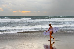 Woman surfer walking on the beach