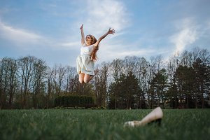 Young woman jumping barefoot on green meadow. Freedom and health in megapolice concept