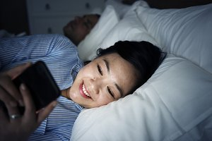 Asian woman using phone on a bed