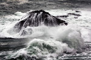 rocky islet with giant waves