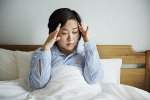 A woman waking up with headache