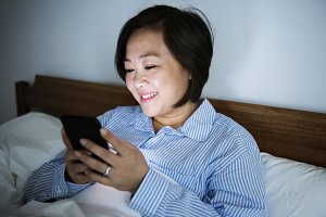A woman reading from a phone in bed