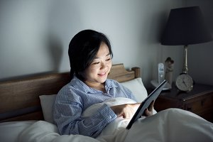 A woman using a tablet in bed