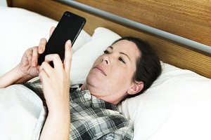 A woman using a mobile phone in bed