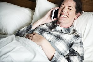 A woman calling someone in bed