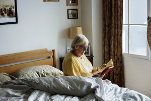 Senior woman reading on a bed