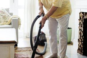 Senior woman vacuuming a carpet