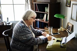 Senior woman writing on a paper