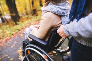 Senior couple with wheelchair in autumn forest.