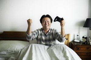 A man playing a video game in bed