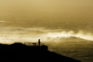 men look at sunset giant waves sea