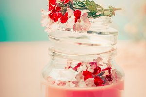 Cream in glass jar with flowers