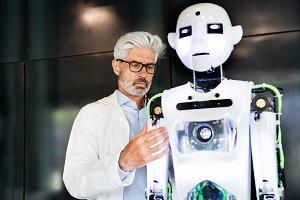 Mature businessman or a scientist with robot.
