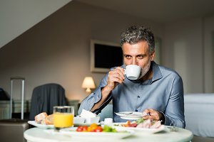 Mature businessman having breakfast in a hotel room.