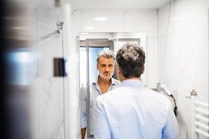 Mature businessman in a hotel room bathroom.
