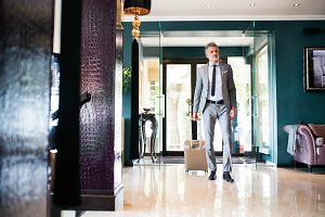 Mature businessman entering hotel with luggage.
