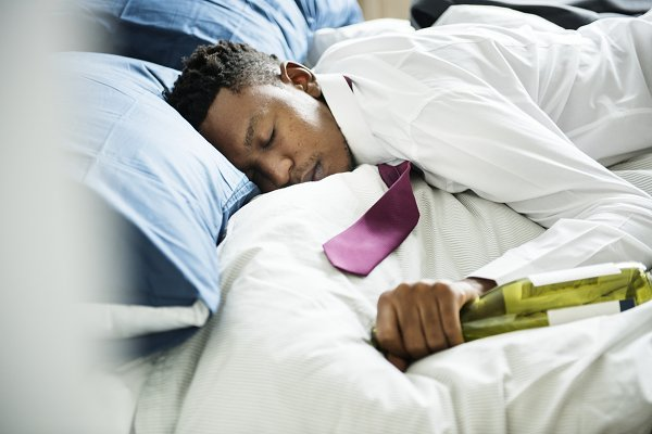 A drunk man passing out in bed