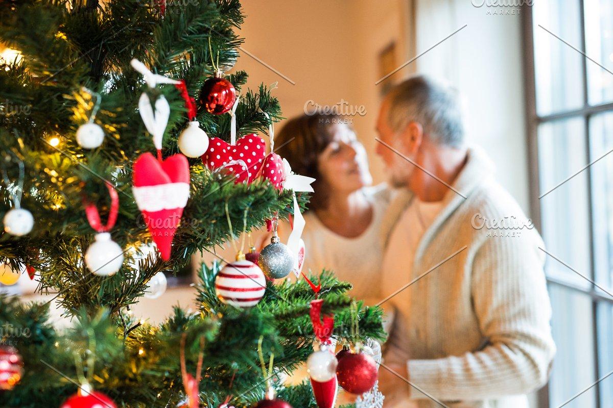 Senior couple decorating Christmas tree at home.