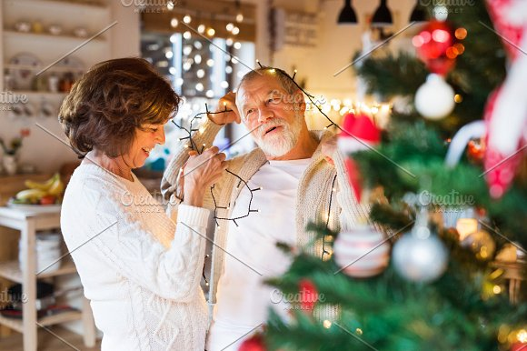 Senior Couple At Home Decorating Christmas Tree