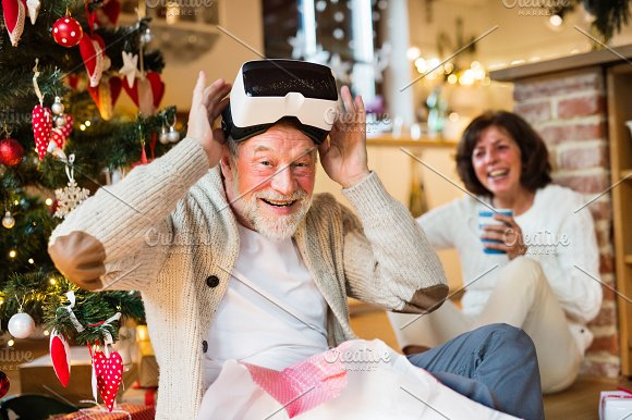 Senior Couple In Front Of Christmas Tree With VR Goggles