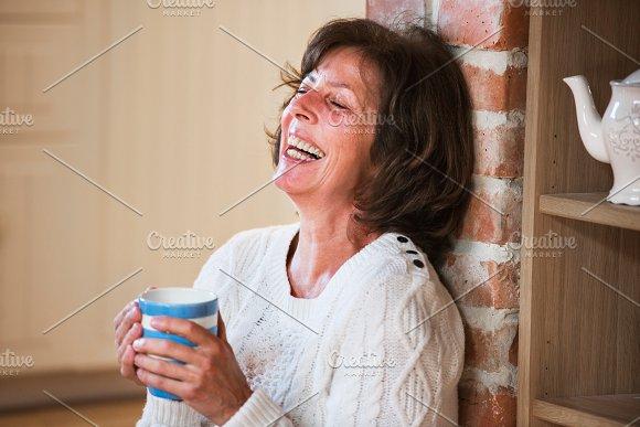 Senior woman at home enjoying hot drink.