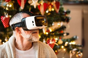 Senior man in front of Christmas tree with VR goggles.