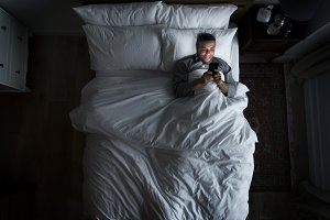 Man on bed using his cellphone