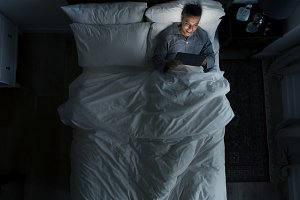 Man on bed using his tablet