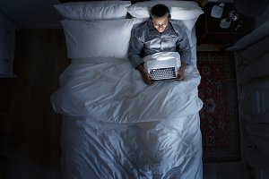 Man on bed using his laptop