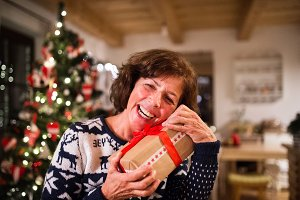 Senior woman in front of Christmas tree holding a gift.