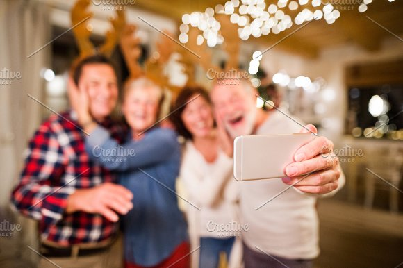 Senior Friends With Smartphone Taking Selfie At Christmas Time