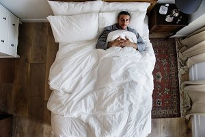 French man sleeping alone on bed