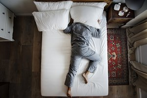 Man sleeping alone on bed