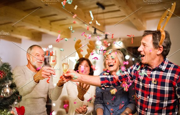 Senior Friends With Confetti And Champagne At The Christmas Tree