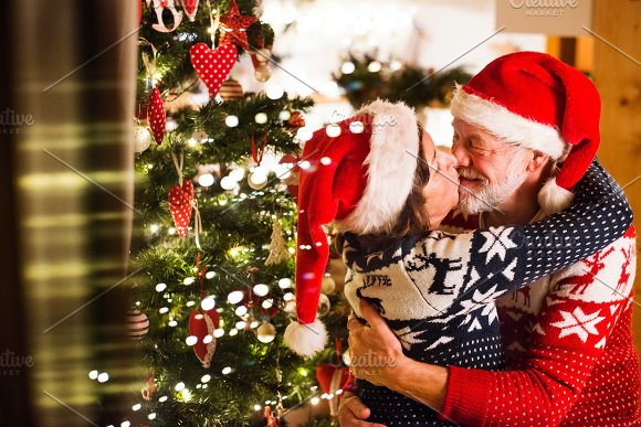 Senior Couple With Santa Hats At Christmas Time