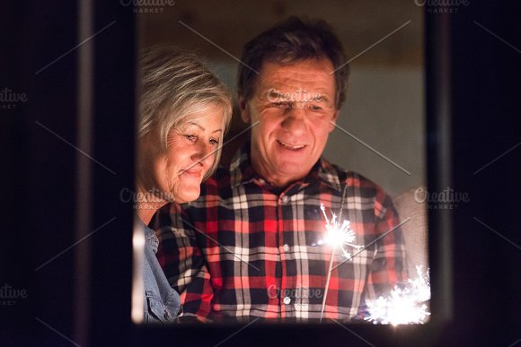 Senior Couple With Sparklers At Christmas Time Having Fun