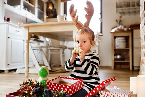 Little girl at Christmas time blowing party whistle.