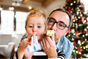 Father with daughter at Christmas time blowing party whistles.