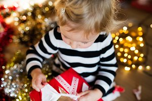Little girl opening Christmas present.