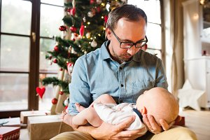 Young father with baby boy in front of Christmas tree.