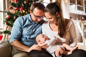 Parents with baby boy in front of Christmas tree.