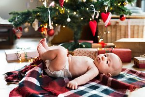 Little baby boy lying under Christmas tree on checked blanket