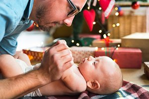 Father with baby boy in front of Christmas tree.