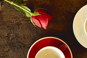 Two empty cups with red roses placed