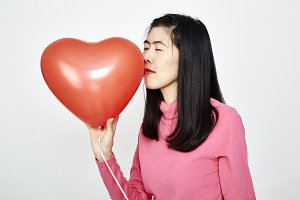 Woman holding red heart shaped ballo