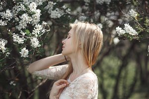 Spring beautiful romantic girl, blonde, enjoying blooming apple trees in swarn sunny day