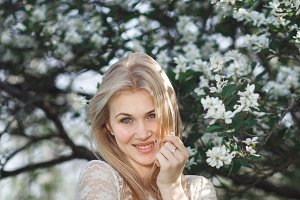 Young cheerful blonde enjoying blossom apple garden. Blooming spring, love, happiness concept